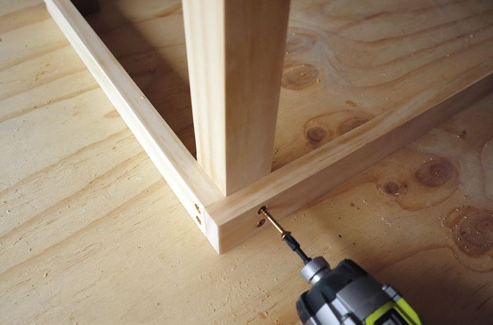 Person drilling screw connecting timber frame to legs