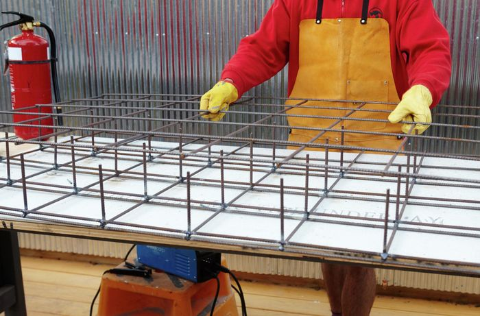 A third sheet of wire mesh laid out over two sheets welded together to make a series of cubes