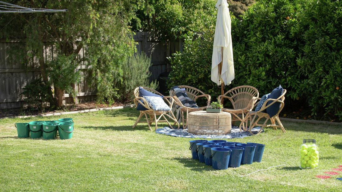 Backyard with two sets of buckets lined up opposite each other.