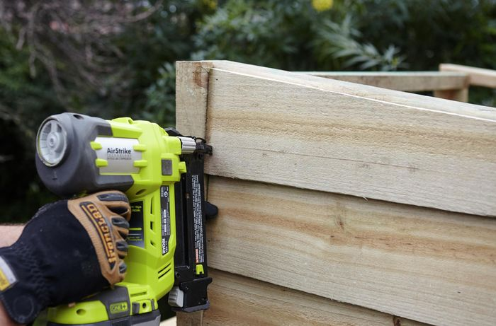 A timber plank being nailed to the side of a chicken coop by a Bunnings team member with a nail gun