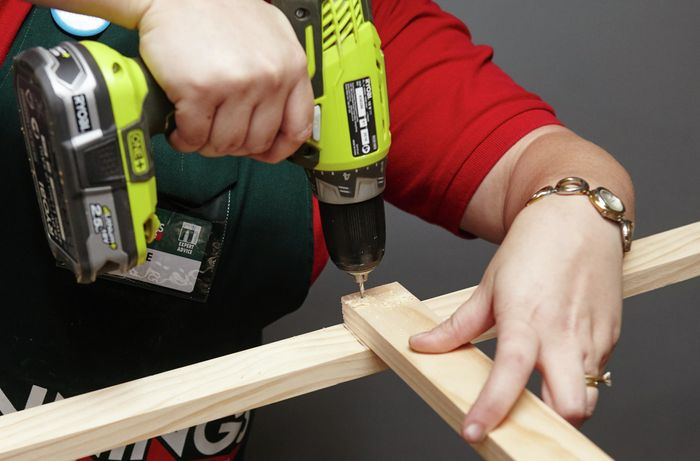 Person drilling bits of timber together to finish book shelf side.