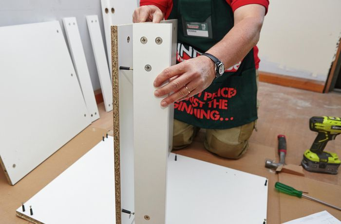 Person attaching rail to shelf panel