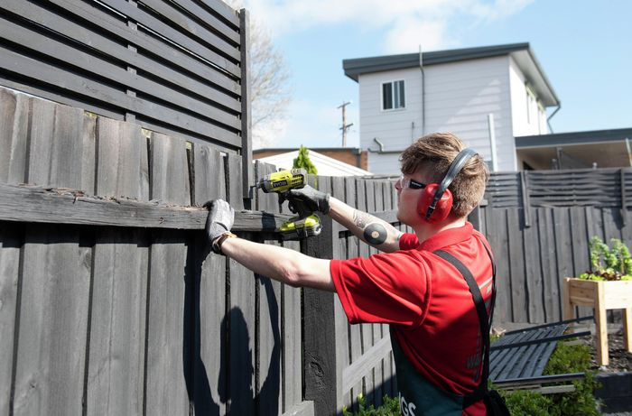 Bunnings team member drilling a fence extension into a wooden fence wearing safety ear muffs, glasses and gloves
