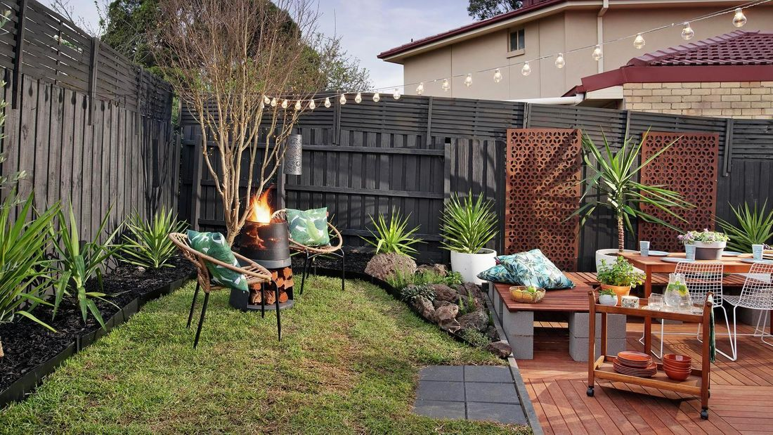 Renovated backyard outdoor area with fire pit, festoon lighting, decking and outdoor furniture.