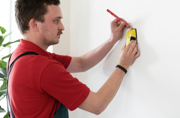 A Bunnings team member finding the stud beam in a wall