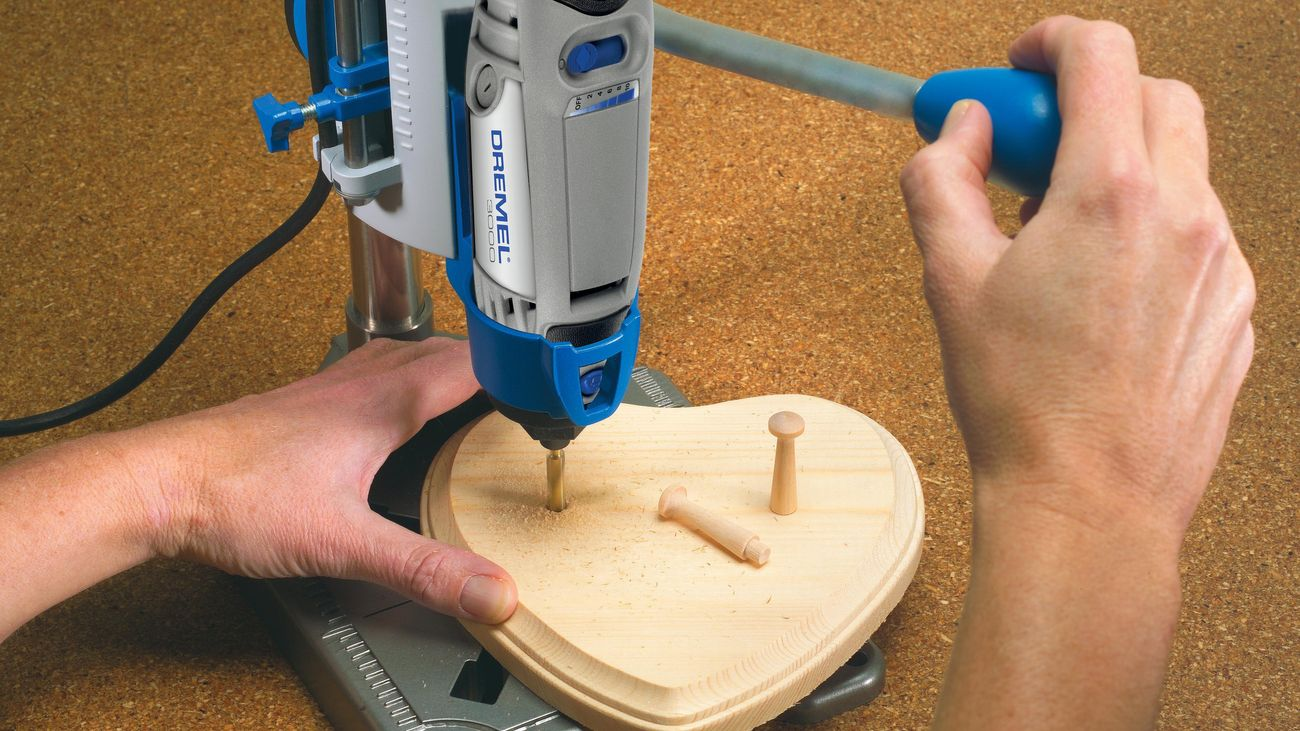 A person using a workstation drill press attachment for a rotary tool