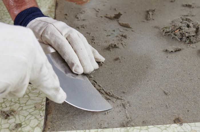 Gloved person scraping paper backing off the floor