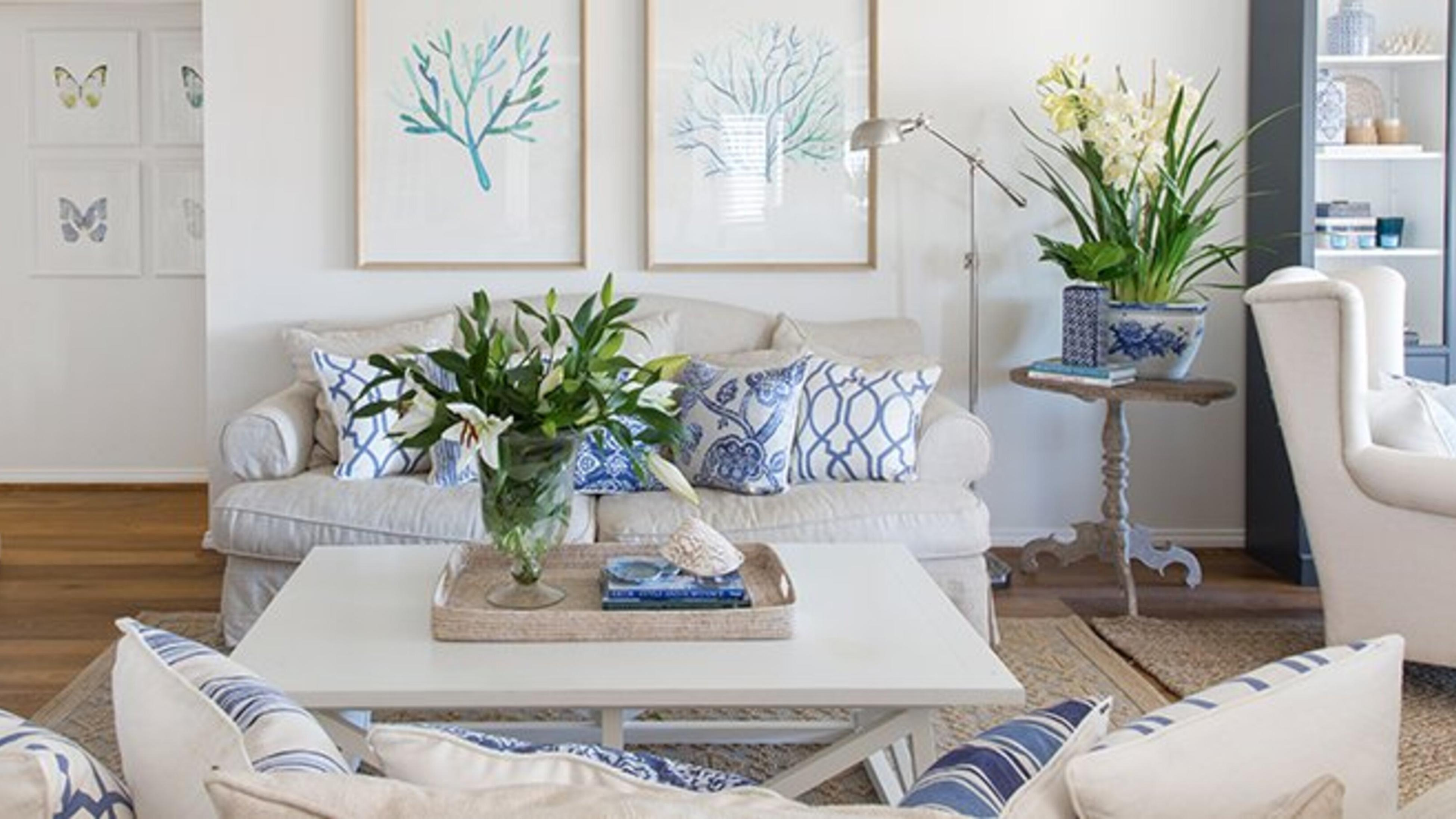 A Hamptons style living area with white couches, blue and white cushions, a white coffee table, wooden floorboards and flowers.