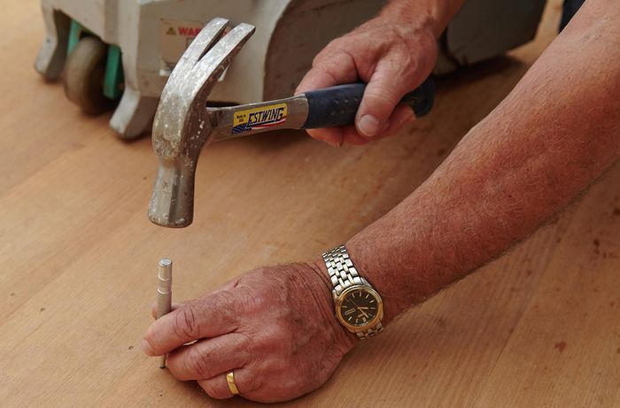 A person using a nail punch and hammer on a hardwood floor