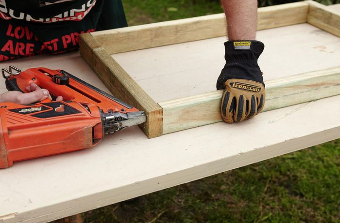 A wooden frame being assembled on a workbench by a Bunnings team member with a nail gun as part of a chicken coop