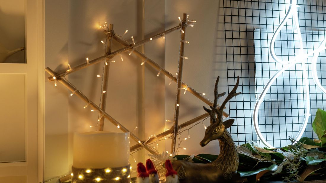 Six-point wooden star wrapped in fairy lights and leant against a wall amongst other various christmas decorations