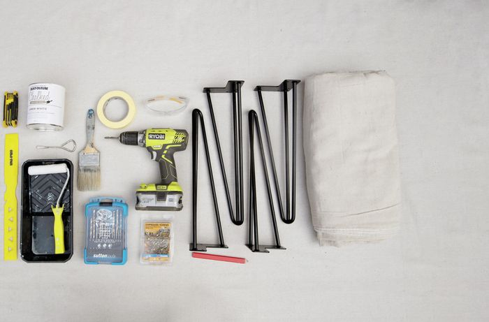 Tools and materials required for the project including drill, paint tray, paint roller and table legs