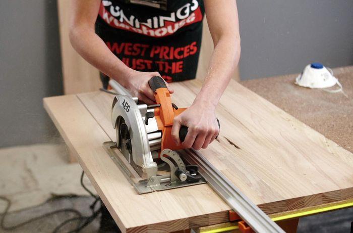 A person cutting a timber panel using a circular saw and straight edge