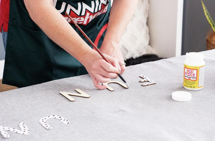 Person painting glue onto wooden letter.
