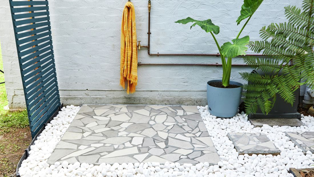 Outdoor shower with crazy paving and plants.