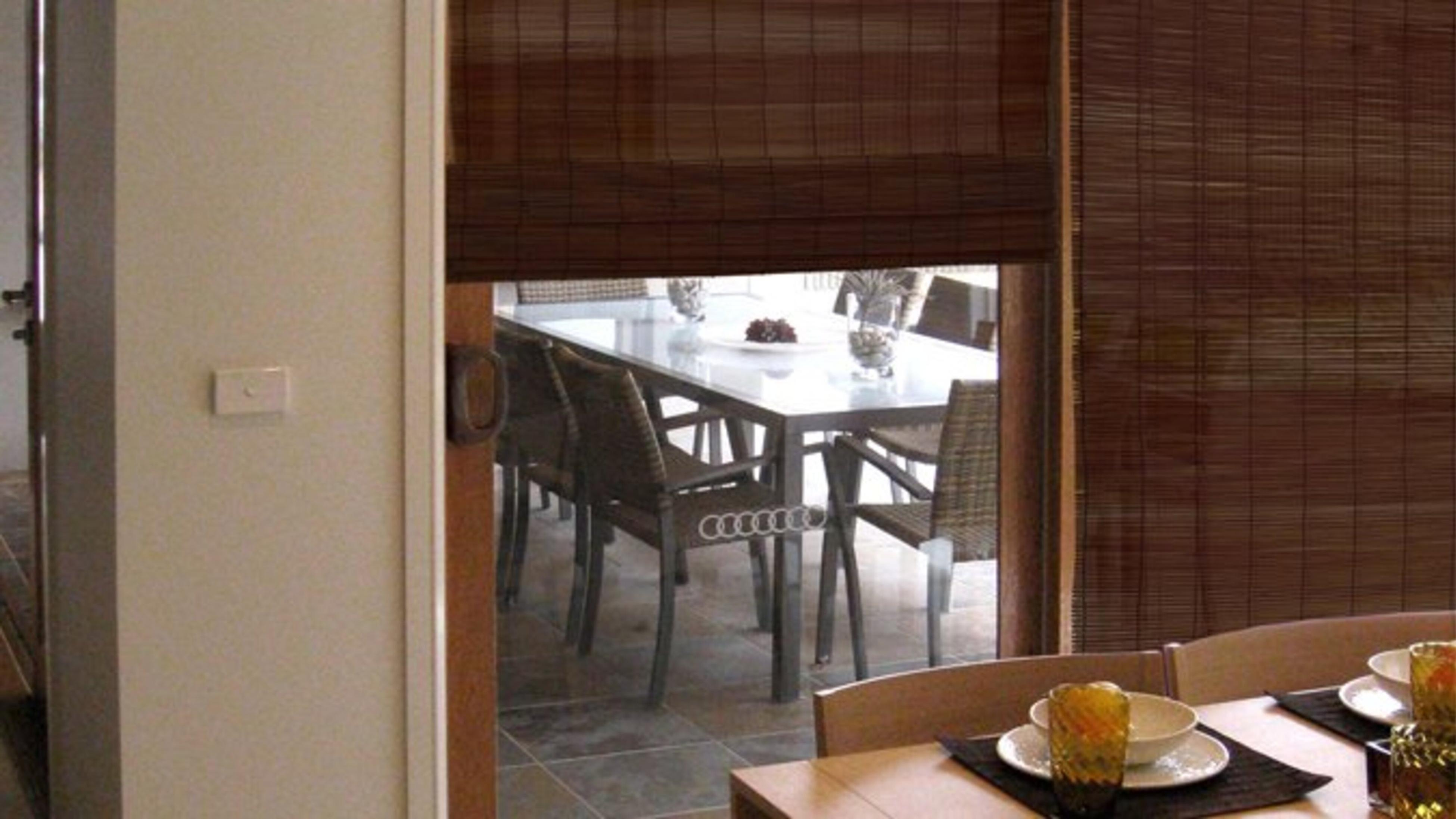 Brown matchstick blinds covering a glass sliding door to an outdoor area.