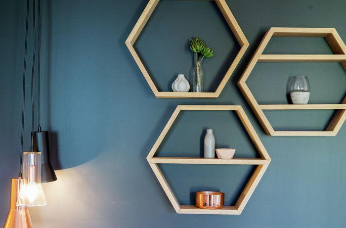 Hexagonal timber floating shelves on a blue wall