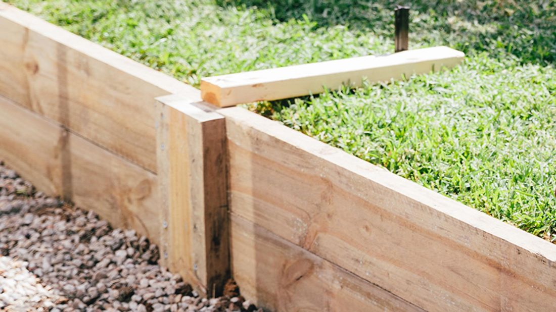 A timber retaining wall with a raised section of lawn