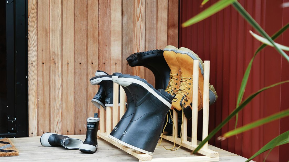 Timber boot rack with a pair of black gum boots