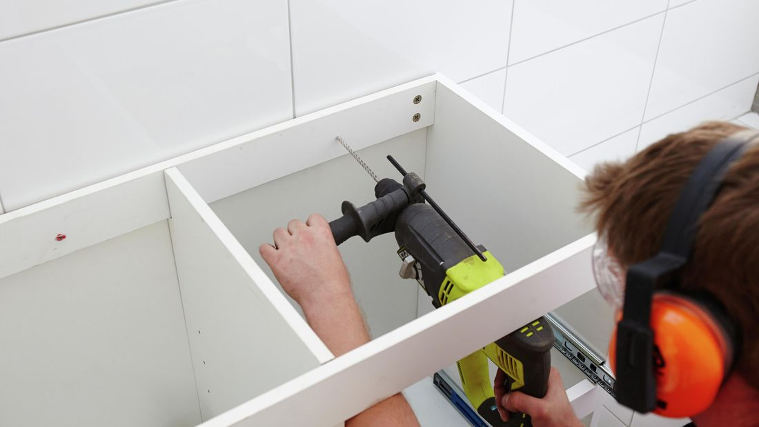 A person using a hammer drill to drill a hole through the back rail of a cabinet into a wall
