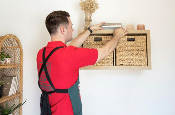 A Bunnings team member placing books, candles and a case on a completed wall mounted cube shelf