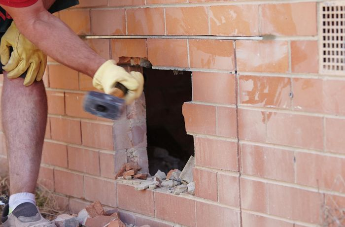 A mash hammer being used to knock bricks out of an opening in the wall