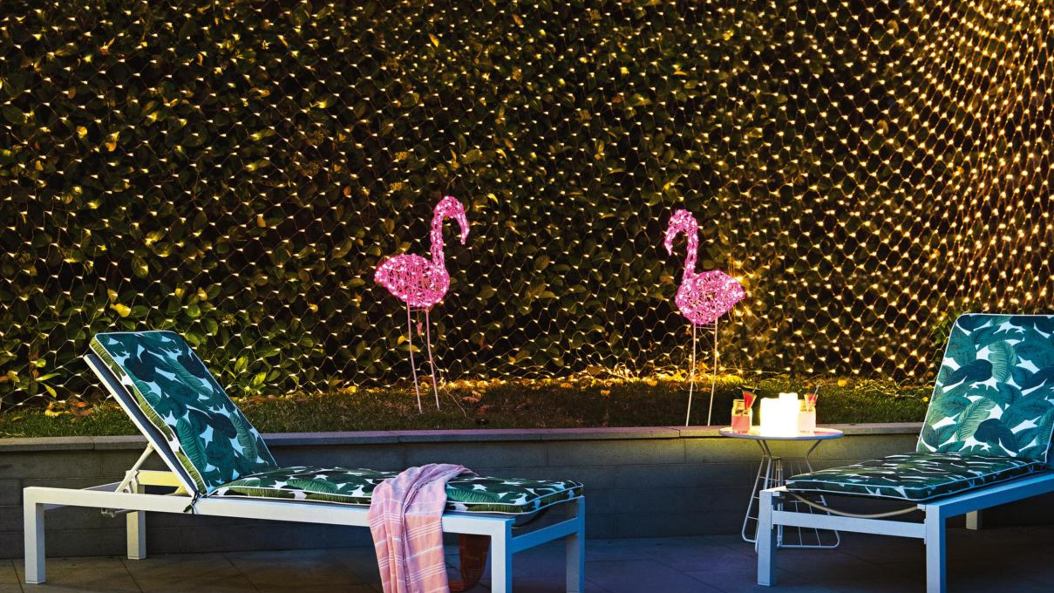 Wall of fairy lights, light flamingos and pool lounges.