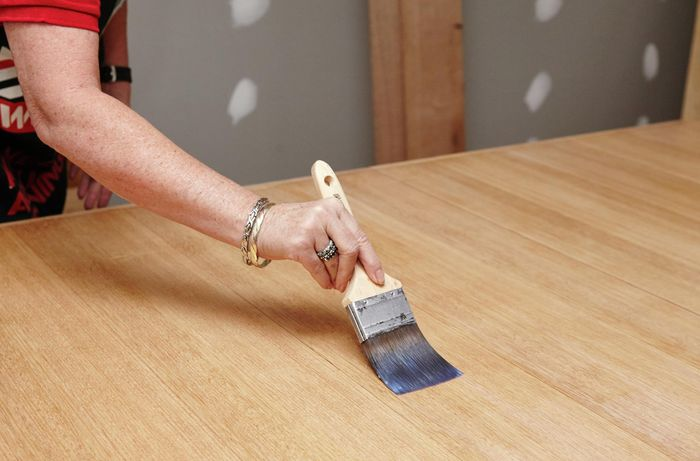 Bunnings Team Member applying a second coat of varnish to the table