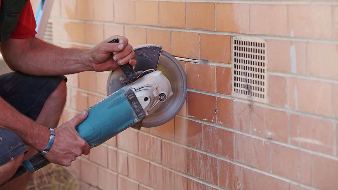 An angle grinder being used to cut vertical lines into a brick wall