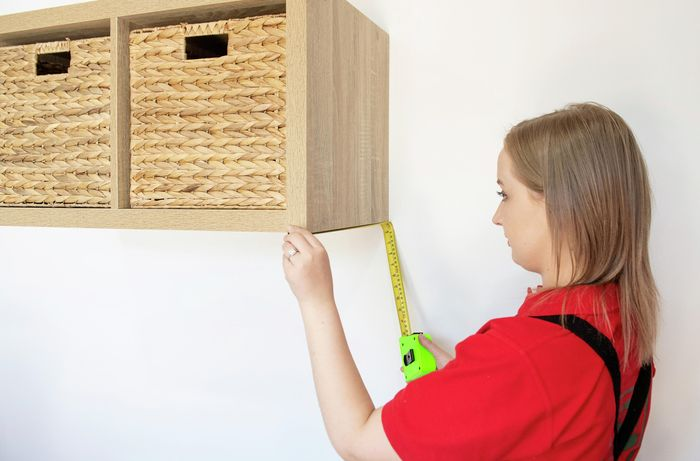 Person using tape measure to measure distance on shelf