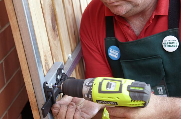 Person screwing a latch keeper to a gate using a cordless driver