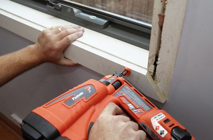 A person attaching architrave under a window with a nail gun