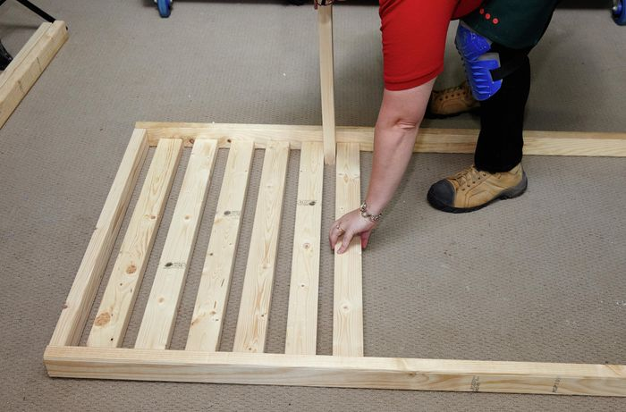 Person building timber bed frame
