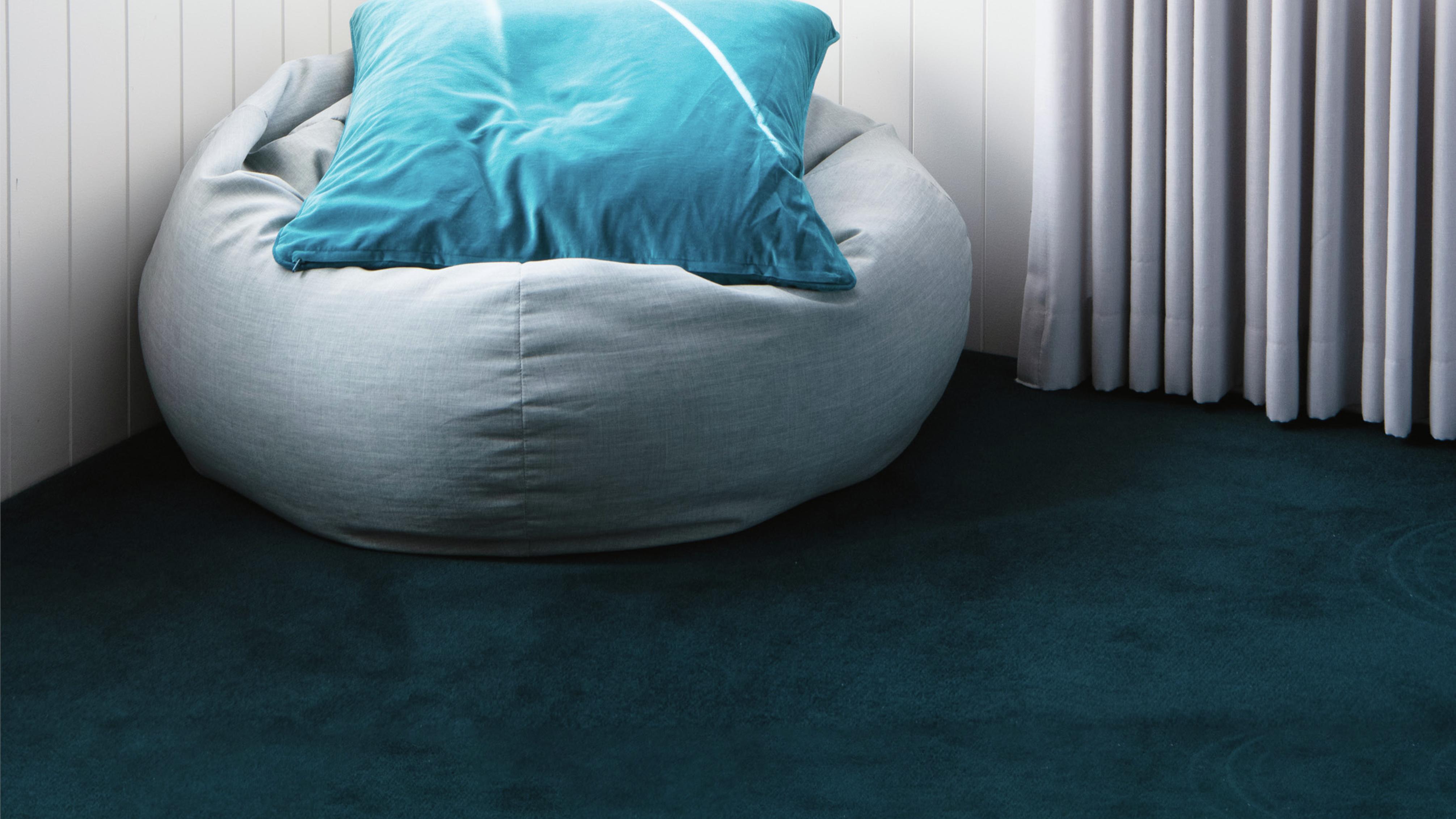 Kids room featuring blue carpet, a bean bag and blue cushion