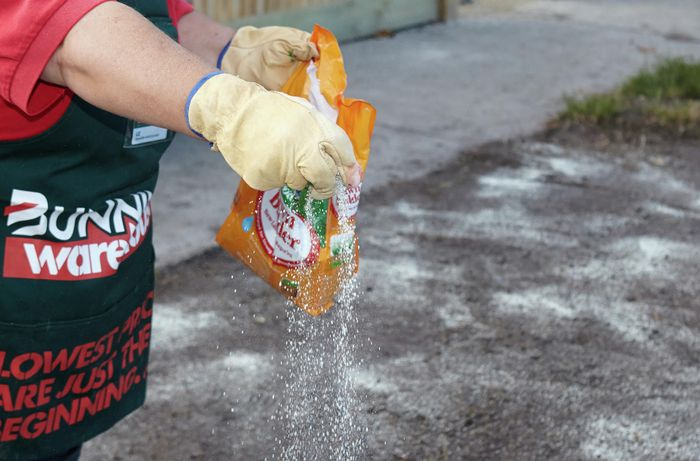 A person applying fertiliser onto the soil by hand