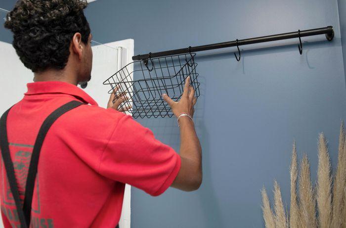 A Bunnings team member hanging a metal basket on a mounted bathroom rail