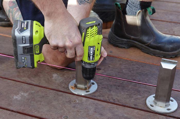 Person drilling mini post into the deck.