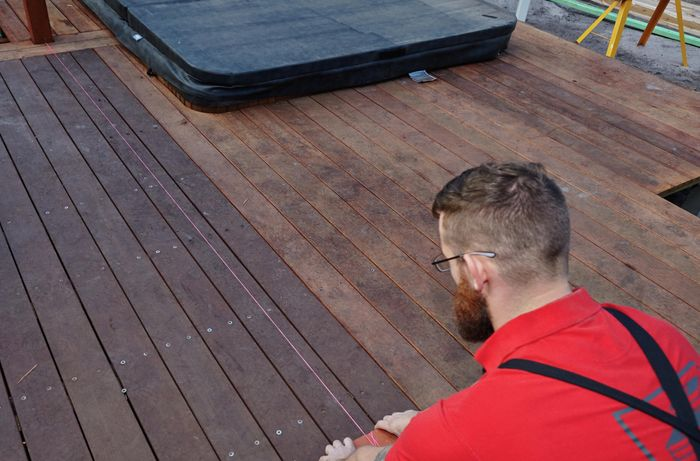Person setting out string line on a deck.