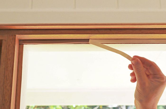 Backing paper being removed from a length of window seal applied to the edge of a window