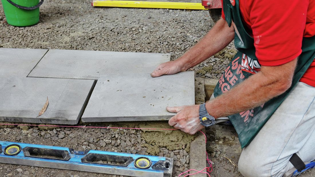 A person laying a paver on the ground alongside other pavers.
