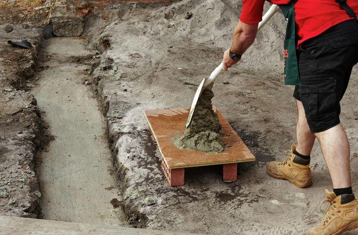 Person shovelling mortar.