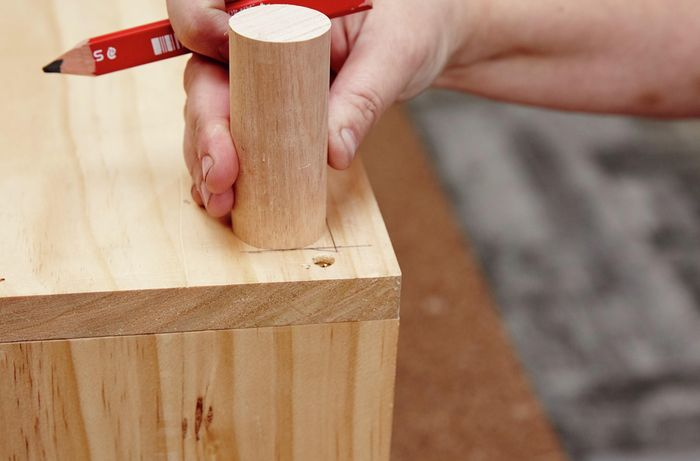 Wooden dowel legs being positioned on the underside of a kids wooden storage bench