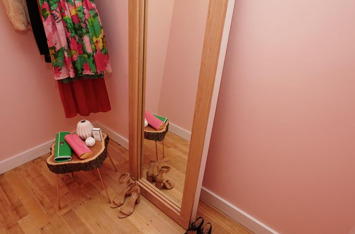 A narrow dressing room with clothes, shoes and a full-length mirror in a timber frame