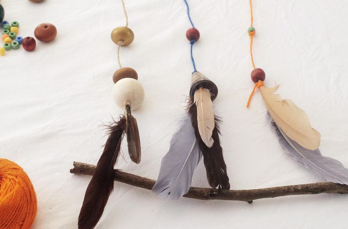 A completed nature hanging with feathers, beads and three pieces of string.