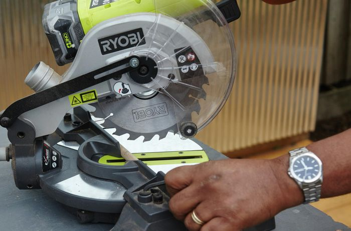 Person using drop saw to cut piece of timber