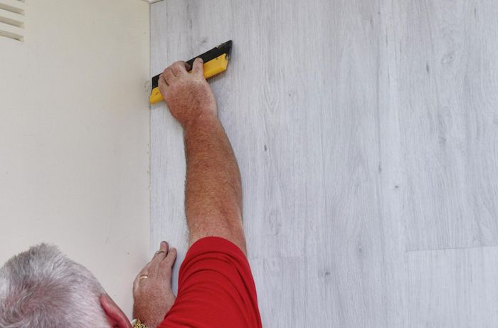 Faux wooden panels being pressed firmly into place on a feature wall