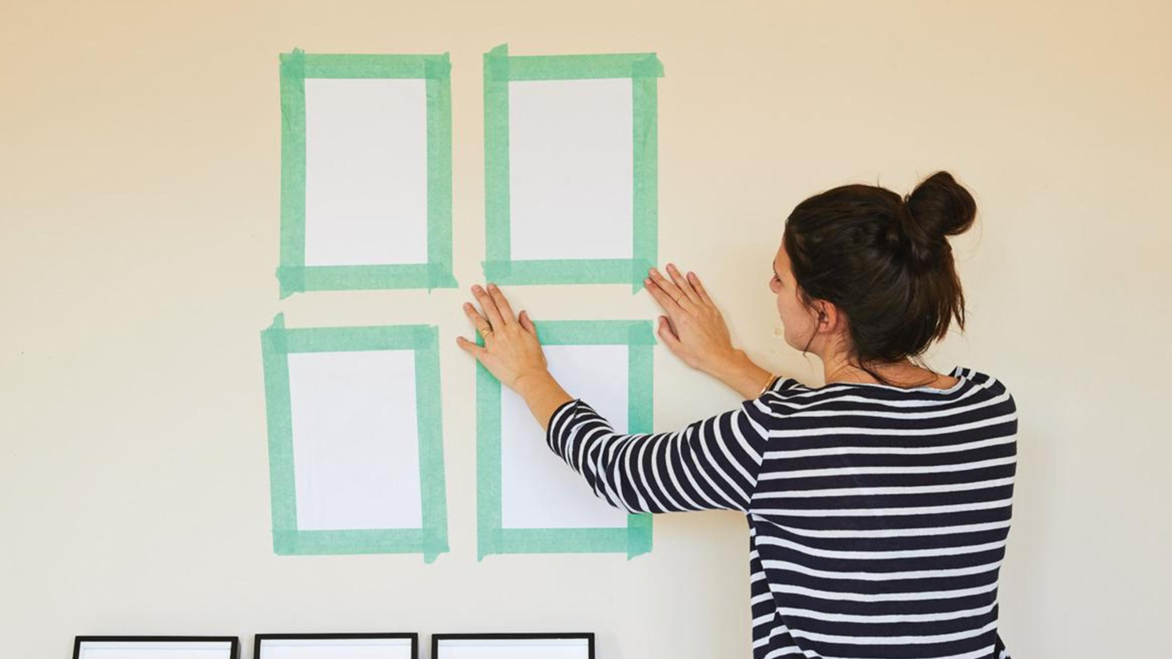 A woman using tape to plan where she will hang the frames.