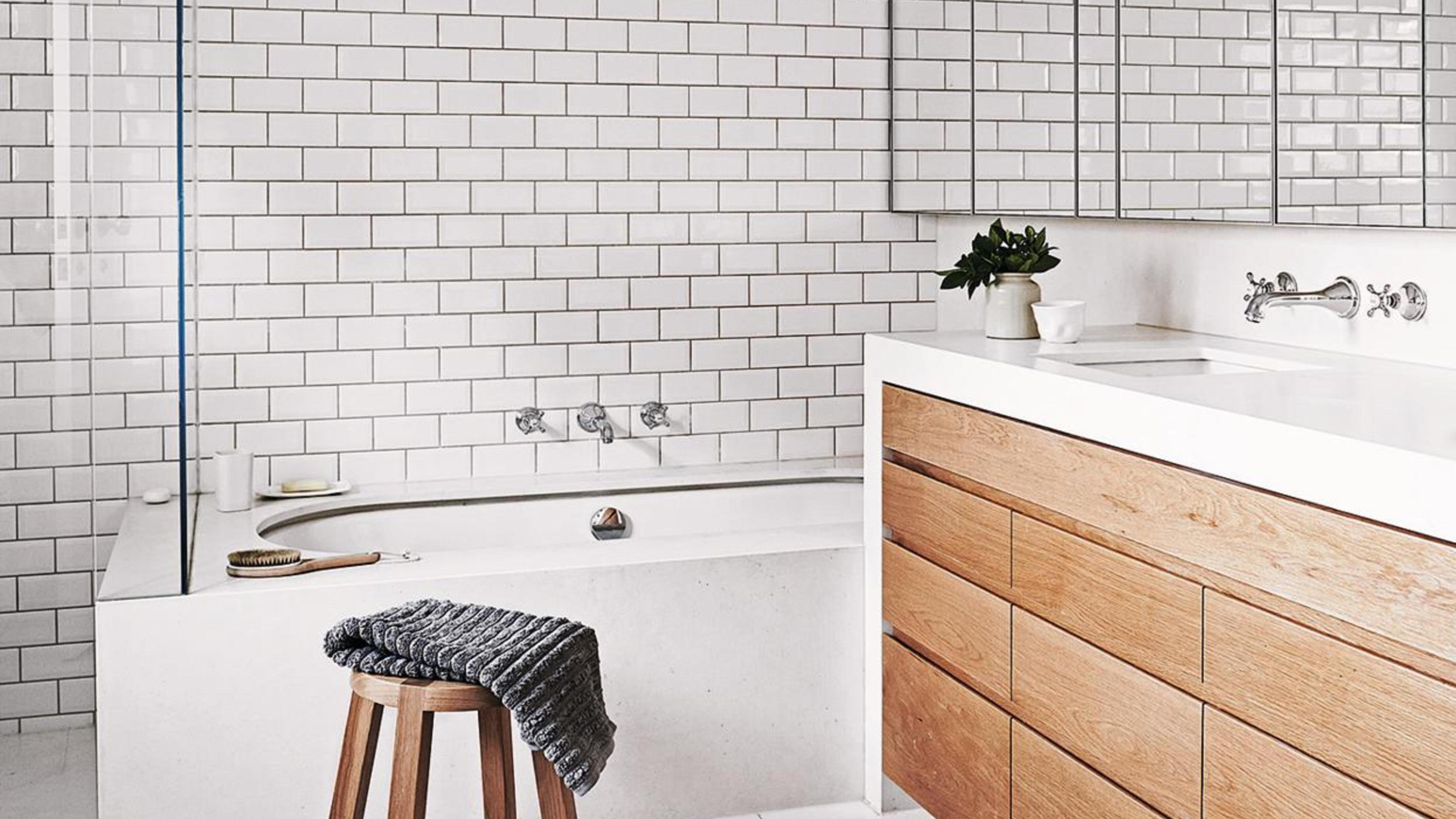 Bathroom featuring white tiled walls.