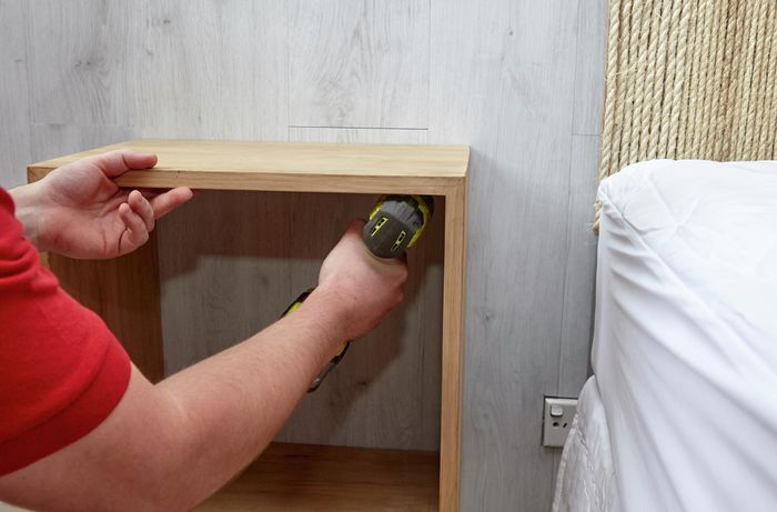 Person attaching shadow box frame to wall with a drill.