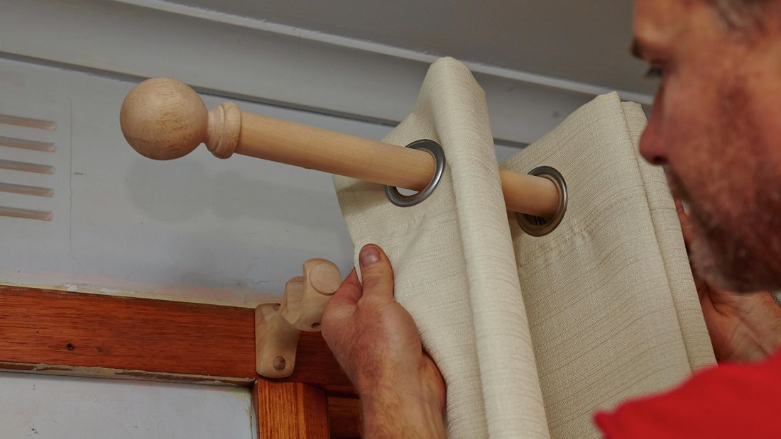 Person fitting curtains to curtain rod.